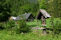 Old wooden house and a wooden cross in the foreground in the village of Hinterwildalpen in the mountain region Gesäuse Styria Austria