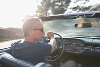 Man driving classic convertible car