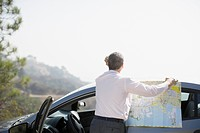 Man looking at map by car