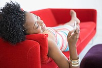 Woman text messaging on sofa