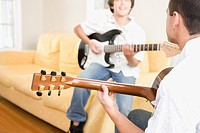 Father and son playing guitar in living room