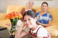 Girl posing at home with mother and grandmother