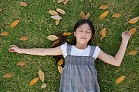Girl relaxing among leaves on grass