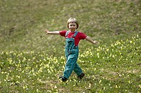 One three-year-old girl running down a meadow in spring