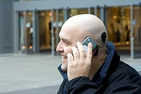 Cochlea implant. Man with a cochlea implant using his mobile phone. A cochlea implant has an external microphone component behind the ear to detect so...