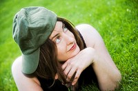 Young woman, wearing a hat, lying on the grass in a park.