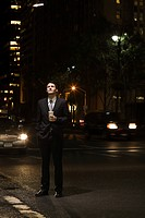 Businessman standing in a road at night (thumbnail)