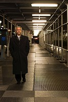 Businessman in a walkway at night