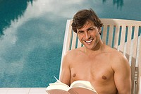 Smiling man reading near swimming pool