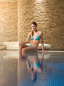 Woman sitting at the edge of a swimming pool