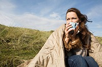 Woman outdoors with blanket and drink