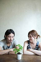 Young couple looking at plant
