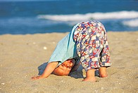 Baby making a headstand in the sand MR