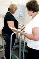 Obesity clinic. Obese woman being weighed during a pre_assessment consultation prior to weight loss bariatric surgery. Surgery can be used to treat ob...