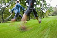 Motion studie of two nordic walker with sticks and sportive clothing walking on a green meadow in the English Garden in Munich