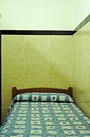 Bed in a hotel bedroom with tiled walls, Barcelona, Catalonia, Spain