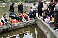 People enclosing the pond and fishing at Fuxing Park, Shanghai, China