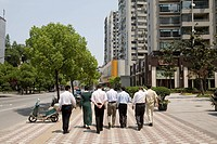 A group of office workers walking on Gubei Road during the lunch break at Hongqiao, Shanghai, China