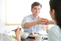 Family having meal in dining room, smiling