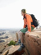 Male hiker sitting on cliff