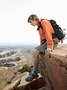 Male hiker looking down on cliff