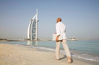 Man walking on beach while holding laptop, Dubai, UAE