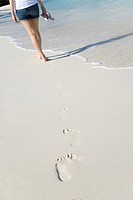 Woman and her footprints on beach sand, Saipan, USA