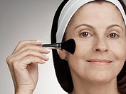 Woman applying make_up with brush