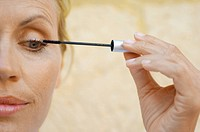 Mature woman applying mascara