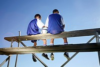 Two boys in soccer kit, sitting on a grandstand _ low angle view. Cape Town, Western Cape Province, South Africa