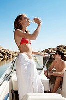 Young couple in motorboat, woman drinking water