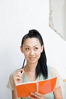 Young woman holding note pad and pencil, looking up, white background