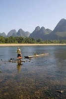 A boatman walking towards the bamboo raft on Li River, Lijiang, Xingping, Guilin, China