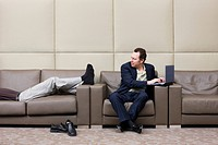 Businessman Annoyed by Man on a Couch