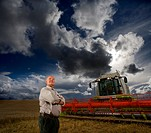 Farmer standing next to combine harvester in wheat field