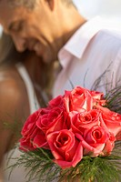 Newlyweds hugging focus on flowers