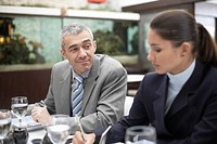 Businessman looking at woman making notes