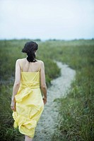 Young woman walking on path rear view