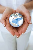 Close up of womanÆs hands cupping crystal ball globe with surgeons