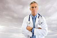 Portrait of doctor in lab coat with overcast sky in background