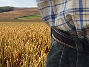 Close up of farmerÆs midsection and wheat field