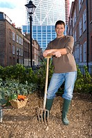 Man posing with pitchfork in urban rooftop garden