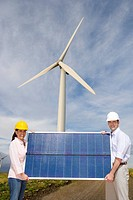 Man and woman in hard hats holding solar panel beneath wind turbine