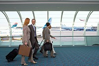 Business people walking down airport concourse