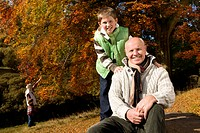 Portrait of grandfather and grandson in woods with autumn leaves (thumbnail)
