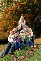 Portrait of multi_generation family and dog in woods