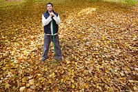 Portrait of man with rake standing in autumn leaves