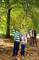 Boy and girl throwing autumn leaves in air
