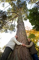 Portrait of couple hugging tree trunk