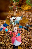 Girl throwing autumn leaves in air with family in background